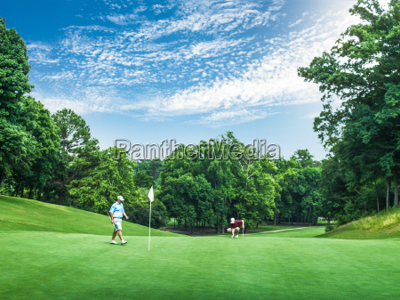 two young male golfers competing on
