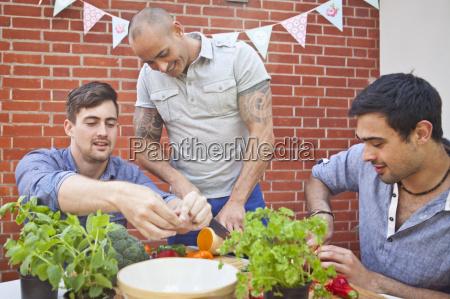 three male friends chopping and preparing