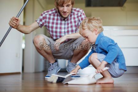 boy helping father sweep floor