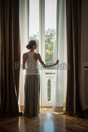 elegant young woman looking out of