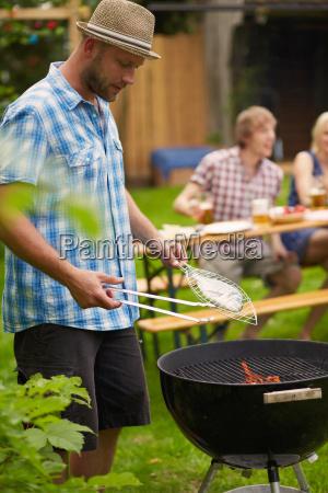 mann grillt fisch auf grillen im