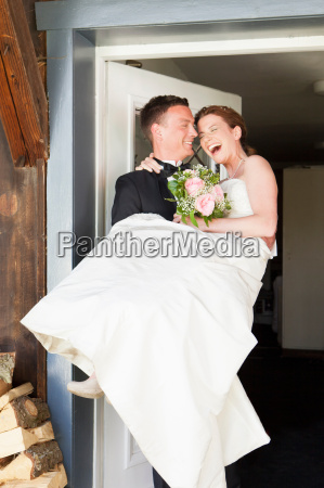 groom carrying bride across threshold