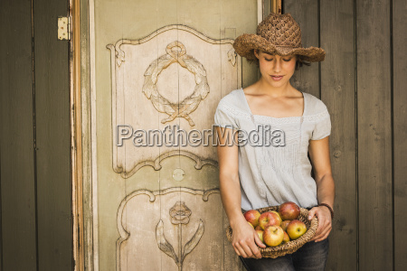 young woman wearing straw hat leaning