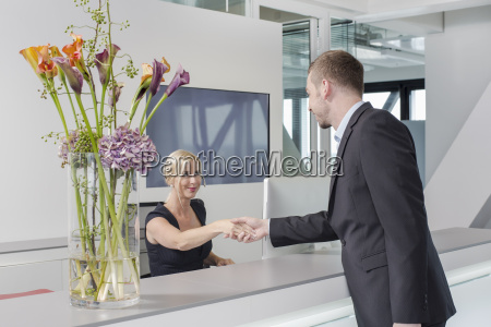 man shaking hands with female receptionist