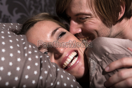couple in bed laughing close up