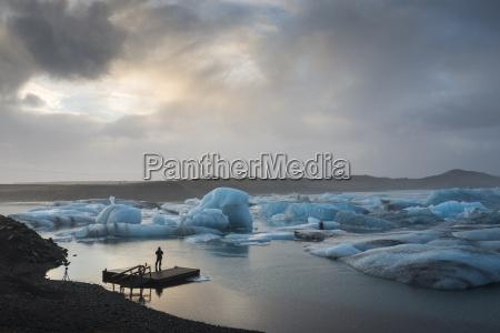 tourist photographing by blue icebergs jokulsarlon