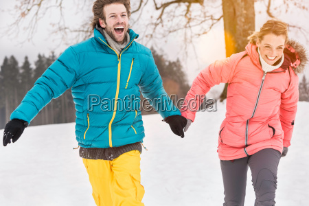 mid adult couple running in snow