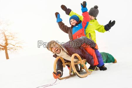 man with two boys on toboggan