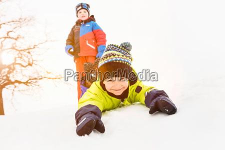 boy lying on snow with friend