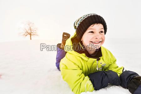 portrait of boy lying on snow