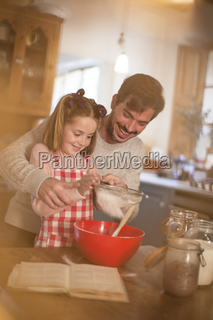father and daughter sifting flour into