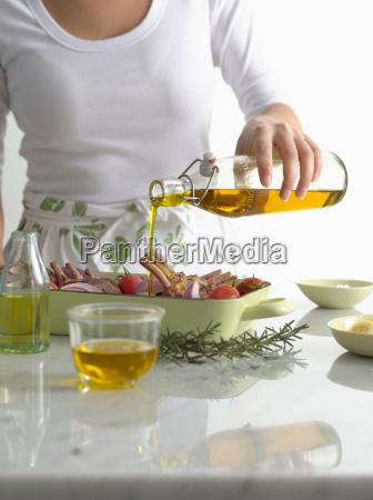 frau giesst olivenoel ueber bratsche