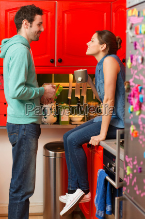 young couple in kitchen woman sitting
