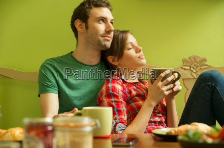 young couple in kitchen relaxing over