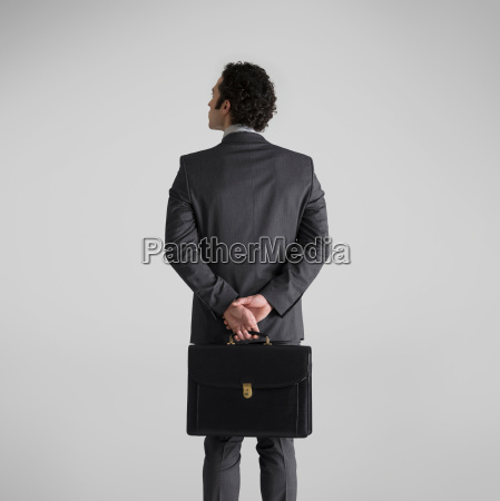 man holding suitcase rear view