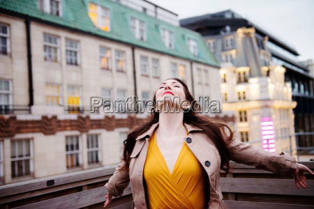 businesswoman standing on urban rooftop