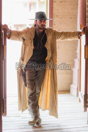cowboy standing in saloon doorway on