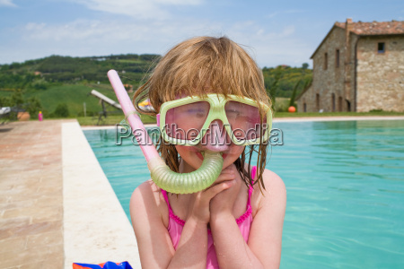 girl by swimming pool wearing snorkel