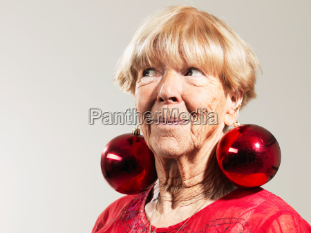 senior woman wearing red baubles as