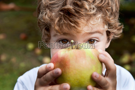 close up of boy holding apple