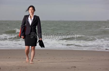businesswoman walking barefoot on beach