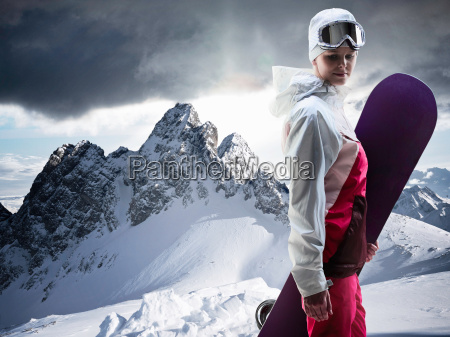 woman with snowboard on snowy mountain