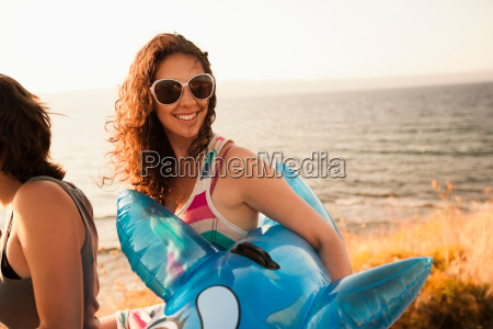 woman carrying inflatable toy on beach
