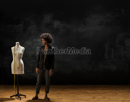 businesswoman standing by blackboard with tailors