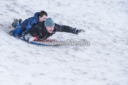 father and son sledging downhill in