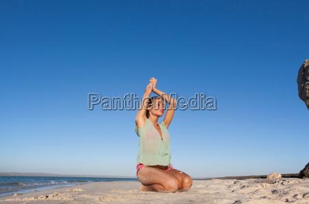 woman in bikini kneeling on beach