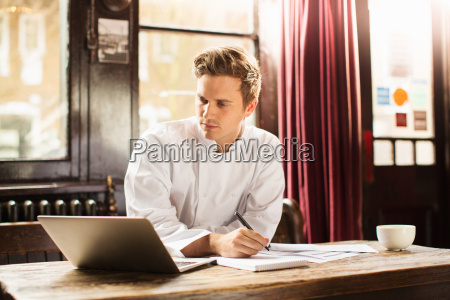 junger mann traegt kochuniform mit laptop