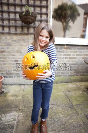 smiling girl holding heavy halloween pumpkin