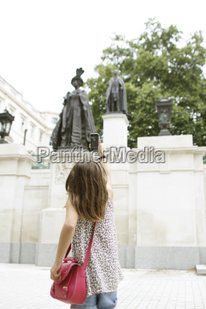 young girl taking picture of queen