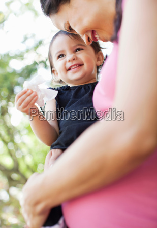 pregnant mid adult woman holding daughter