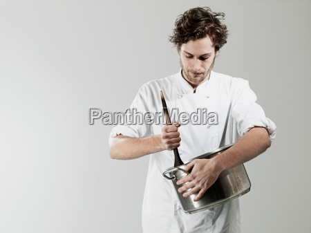 chef stirring in pan against white