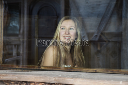 bare shouldered young woman looking out