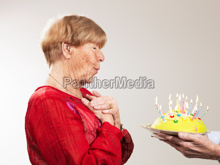senior woman receiving birthday cake against