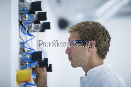 male scientist making control panel adjustment