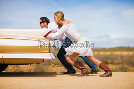 couple pushing a car