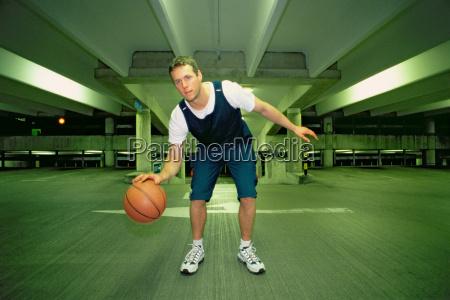 man bouncing basketball in car park