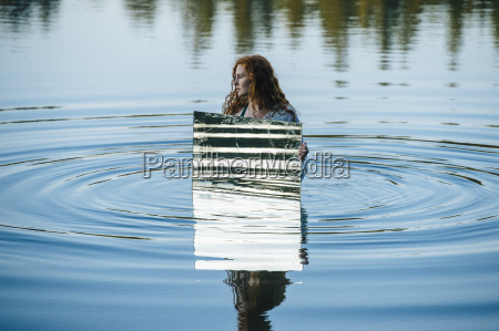 young woman standing in lake holding