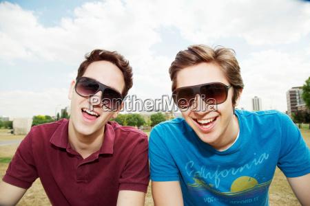 maenner sitzen zusammen im park