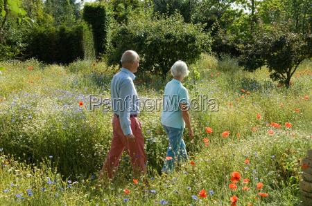 older couple walking in field of