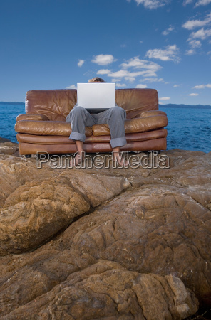 man on couch at beach with
