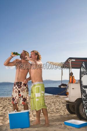 junge maenner am strand trinken bier