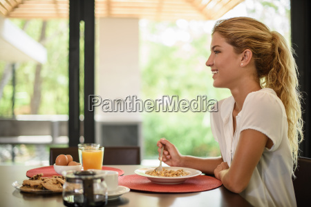 young woman at breakfast table eating