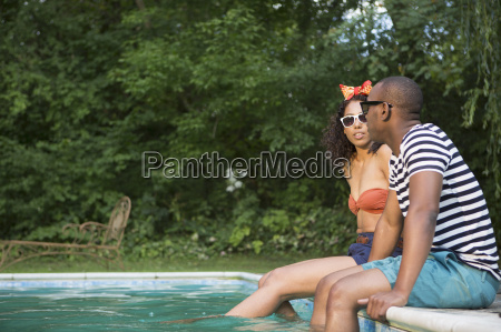 couple dipping legs into pool