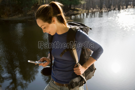 woman with mobile phone by lake