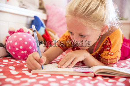 girl lying on bed playing drawing