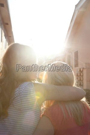 young lesbian couple embracing at sunset